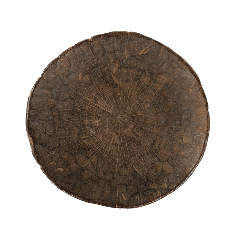 A stool carved from a hollowed-out log section, with a rectangular piercing bisected by a diamond-shaped head motif.