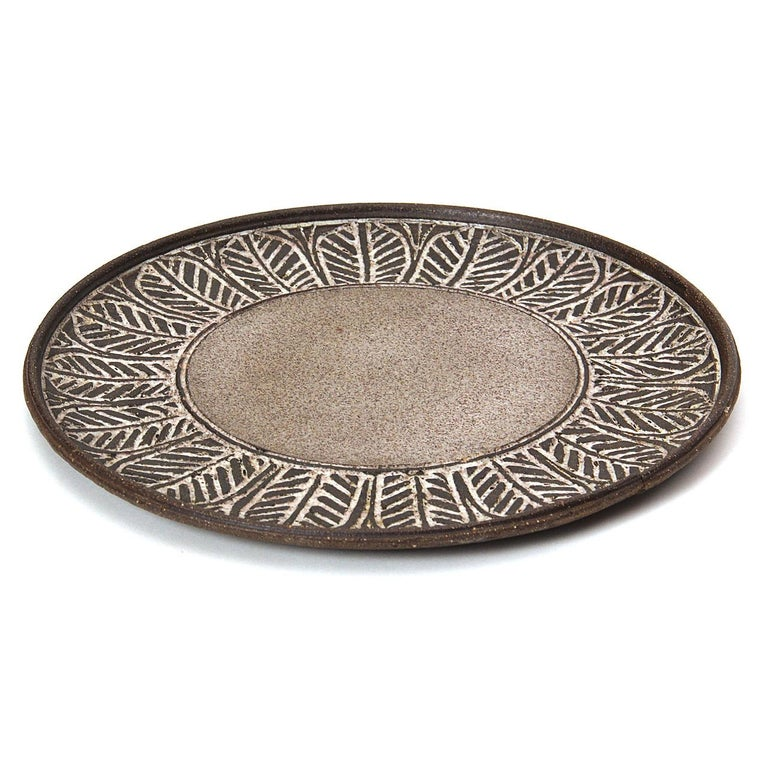 A hand-thrown earthenware ceramic platter with incised leaf motif and stone gray glaze. Signed
