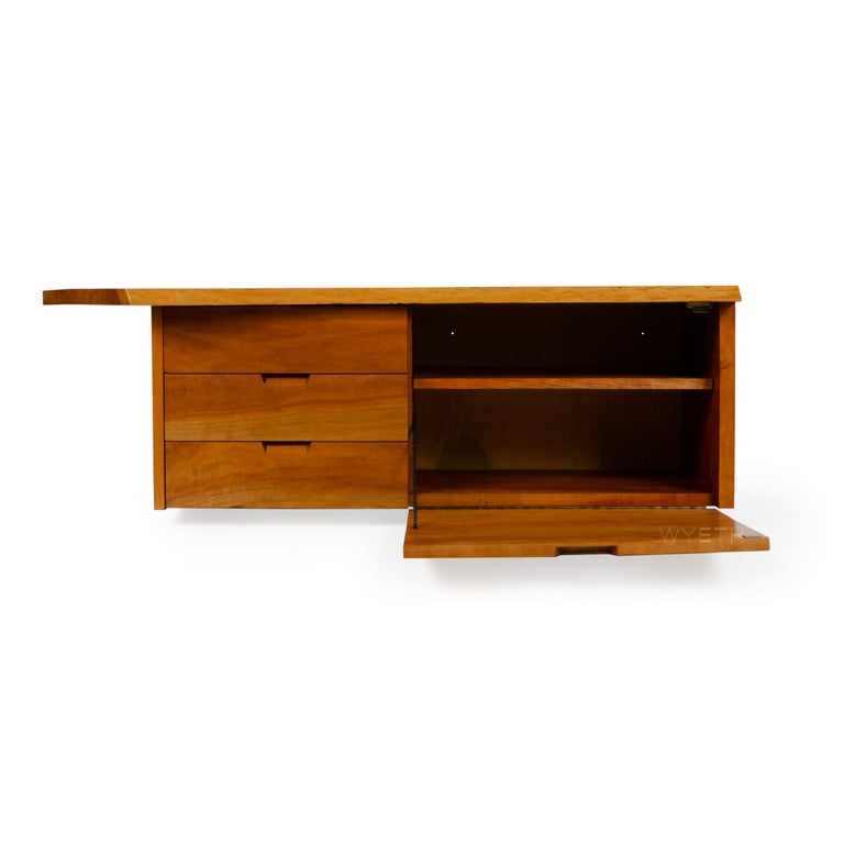 A walnut wall mount cabinet with one drop down door with an adjustable shelf and three (3) drawers, all with integrated handles.