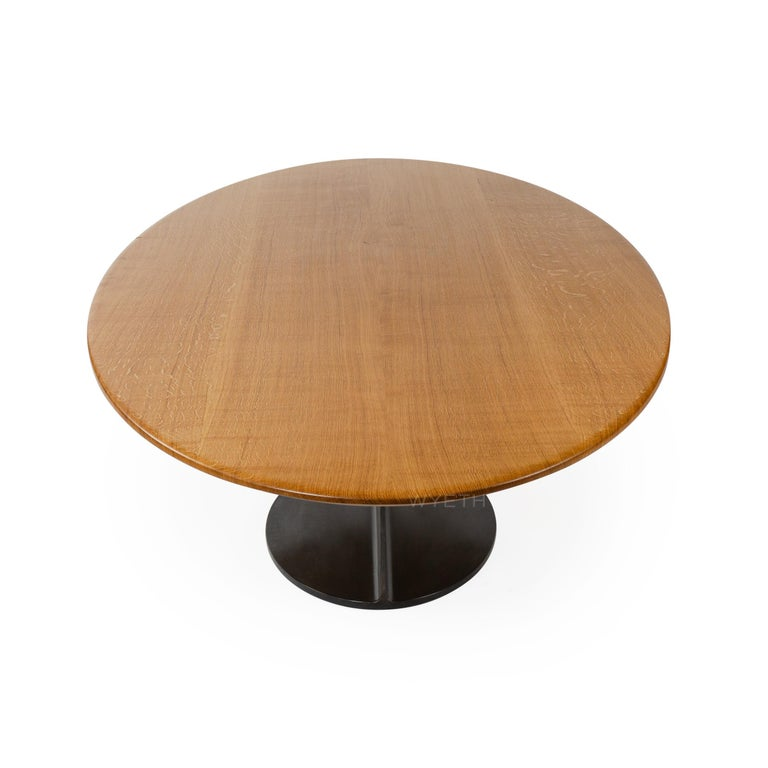 A custom ellipse table with a solid oak top and patinated steel base.