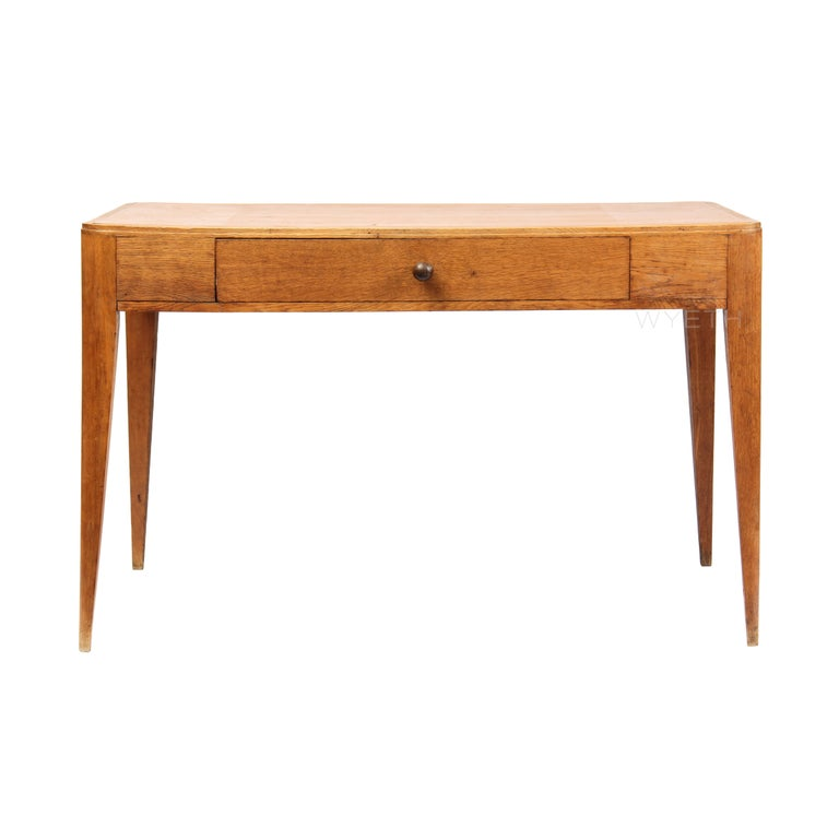 A rectangular oak desk with rounded corners, a tan leather writing surface and a central drawer, on tapered legs.