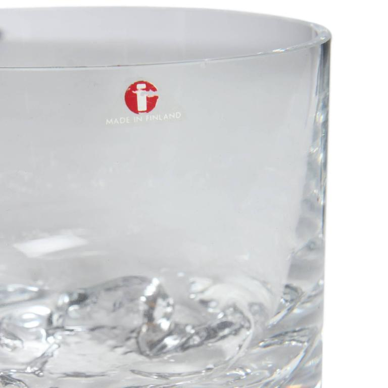 A beautifully executed vessel or ice bowl in the form of a drinking glass having an organic free-form base evocative of winter ice.