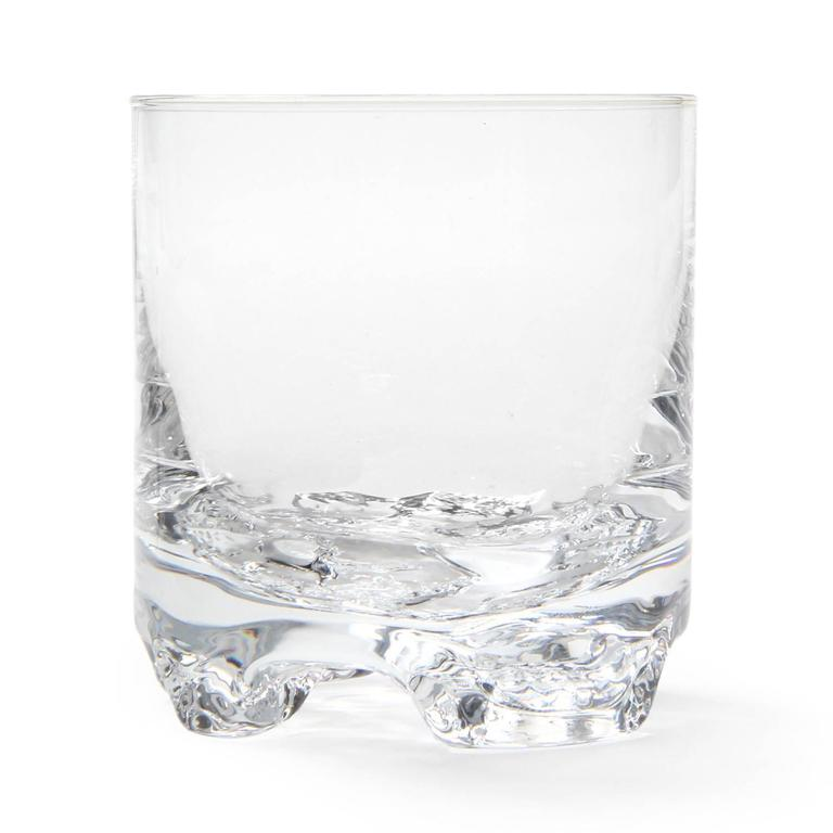 A beautifully executed carafe and four drinking glasses all having organic free-form bases evocative of winter ice.