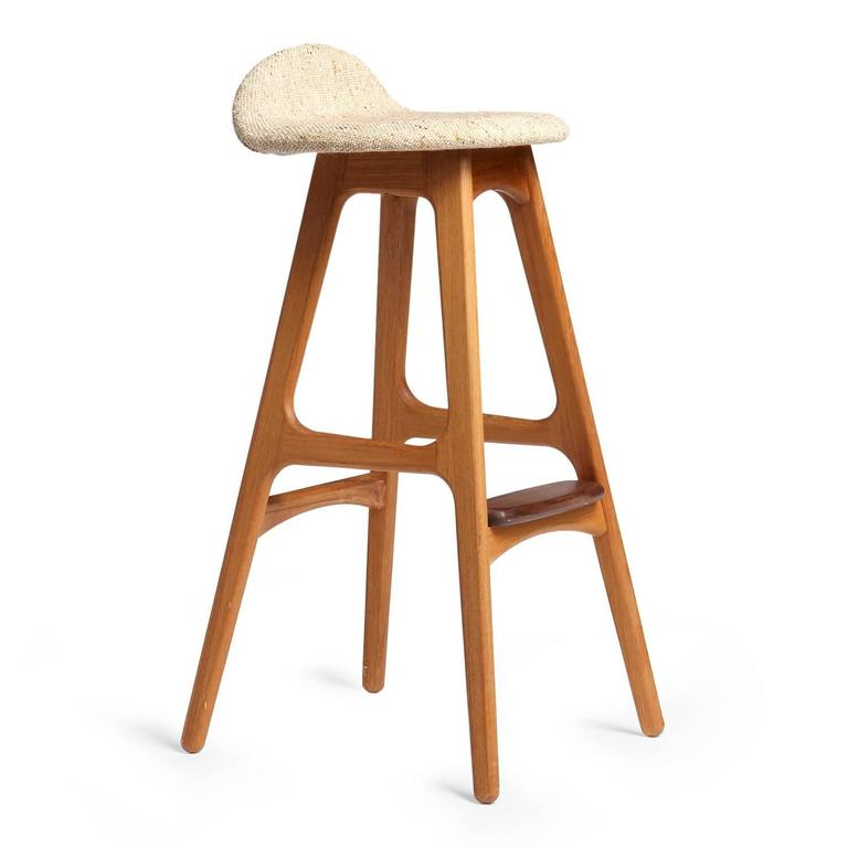 A sculptural and comfortable barstool having splayed legs, a shaped seat with an upturned back support and a rounded projecting foot rest.