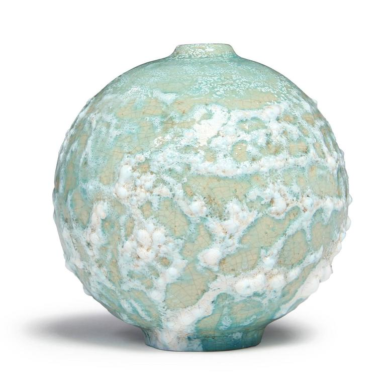 A round studio-made unique ceramic vessel with a raised narrow opening, the form covered with a rich, complex and thickened glaze in tones of celadon, cream and wheat.