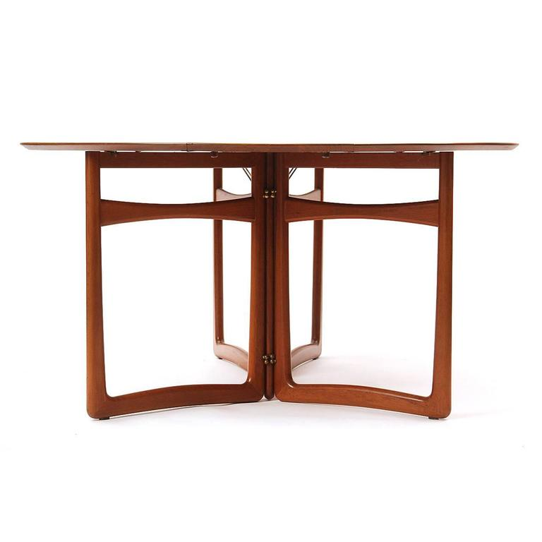 A drop leaf table in solid teak wood that can be used with one or both sides raised, sculptural legs and brass fittings. 18