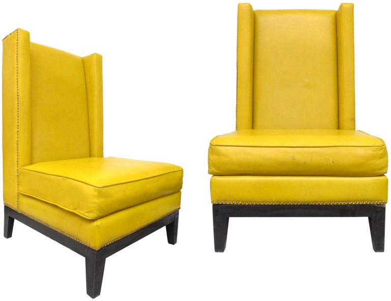 A fantastic pair of leather wingback chairs. Original mustard leather with brass-tacks detailing and ebonized wood base, a wonderfully streamined, modern version of this traditional form with clean lines, a notably deep, comfortable seat and