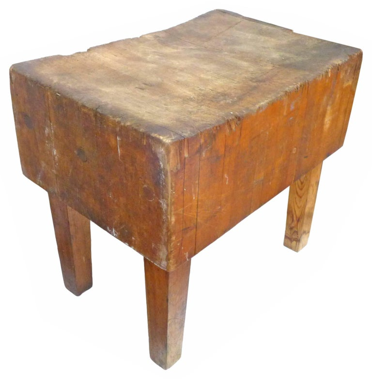 An incredible, vintage, wood butcher-block table. A fantastic piece, beautifully worn from years of use. The top surface showing heavy wear in an irregularly concave surface. Exposed joining bolts at the sides. Square-stock legs hold up the chunky