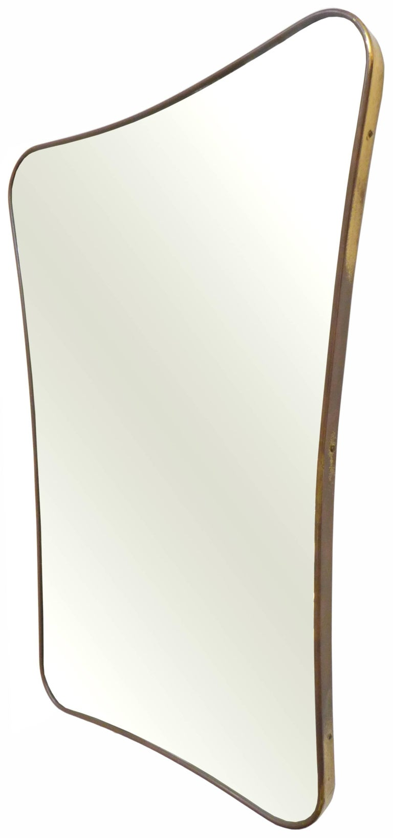 An elegant, Italian, brass-framed mirror. A perfectly patinated, slender brass frame with a gently curving and tapered, biomorphic Silhouette housing an ideally, very subtly aged vintage mirror. A Classic, sophisticated decorative element.