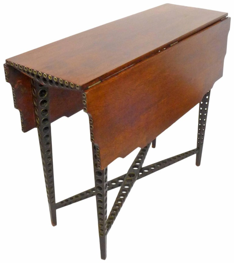 A wonderful and extremely unusual early 20th century drop-leaf table. Multi-directionally perforated, elegantly tapered legs and cross stretchers with graduated circles and brass grommet details. A gently scalloped top detail and additional
