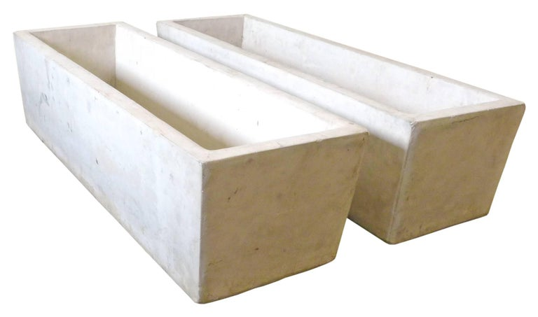 A fantastic pair of architectural, cast-stone planters. Substantial, thick-walled, trapezoidal forms in a pale oatmeal hue. A classic garden element, an impressive matched pair great for use indoors or out.