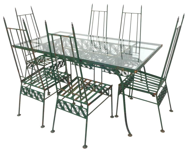 An incredible outdoor dining set for six in wrought iron and glass. A striking group with repeating, graphic, floral details stretched across each piece. High-back chairs sporting brass finials and disc feet. Painted in green with occasional