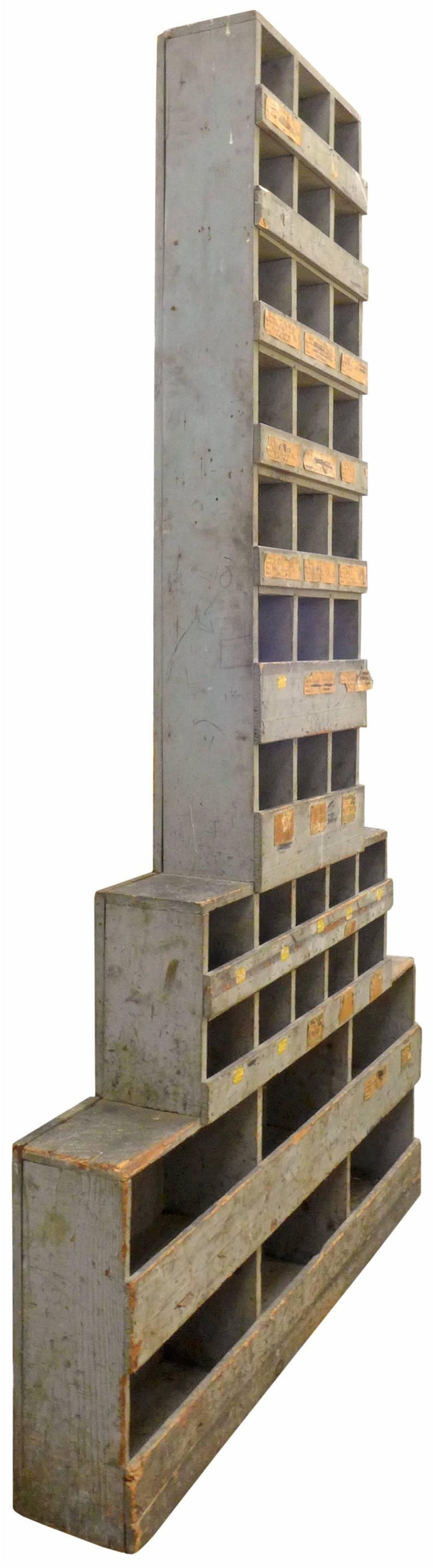 A spectacular, tall and stepped, Machine Age-inspired skyscraper cabinet. Primitive yet architecturally inspired, this unusual form was likely originally used to organize hardware for a hardware store or workshop. A wonderful distressed patina with