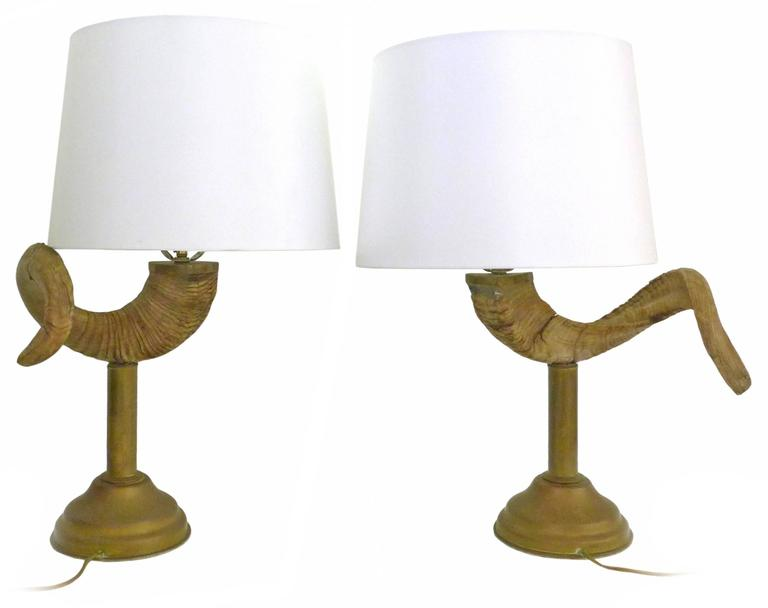 A handsome pair of brass and ram's horn table lamps. Possibly by Chapman Lighting, Classic 1970s American chic; weaving an unexpected yet provocative and powerful organic element with a subtly detailed, perfectly-patinated brass base. Great scale