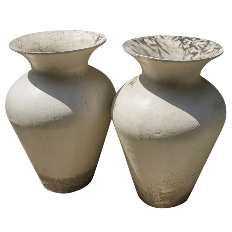 Purchased in France these white cement vases are three feet tall and have curves that provide a chic elegance when combined with light and shadow. Perfect for a home, garden or office environment.