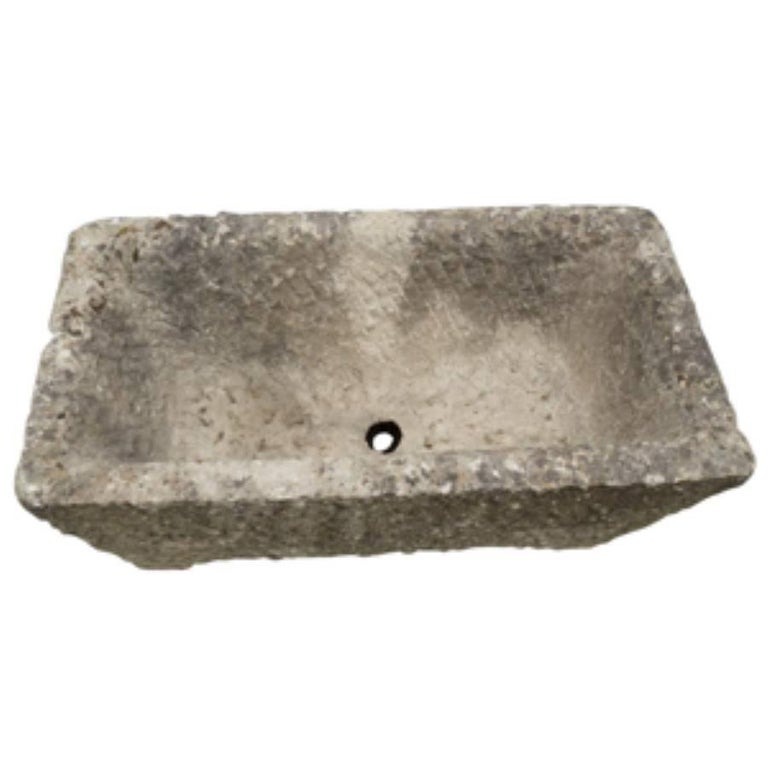 Handsome and heavy, this antique French trough style planter is carved from stone and has a timeless natural beauty. Handcrafted, circa 1800, the trough is a modest size at 31 inches long, 16 inches wide and 14 inches tall. At over two hundred years