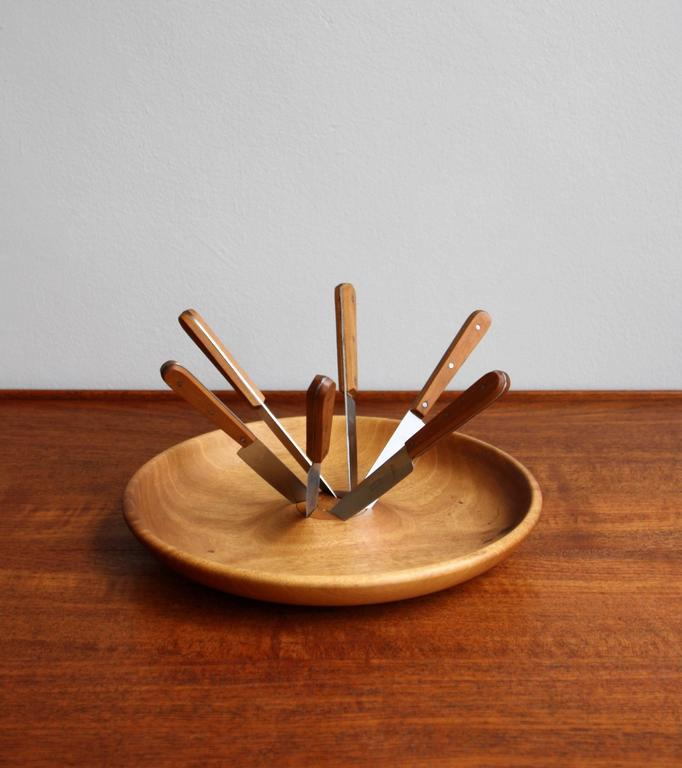 A rare obstmesser/fruit knife set designed and made by Carl Auböck II, circa 1950. The beautifully grained bowl is carved from a solid piece of walnut wood. A set of six stainless steel knifes with walnut clad handles slot into and spiral outwards