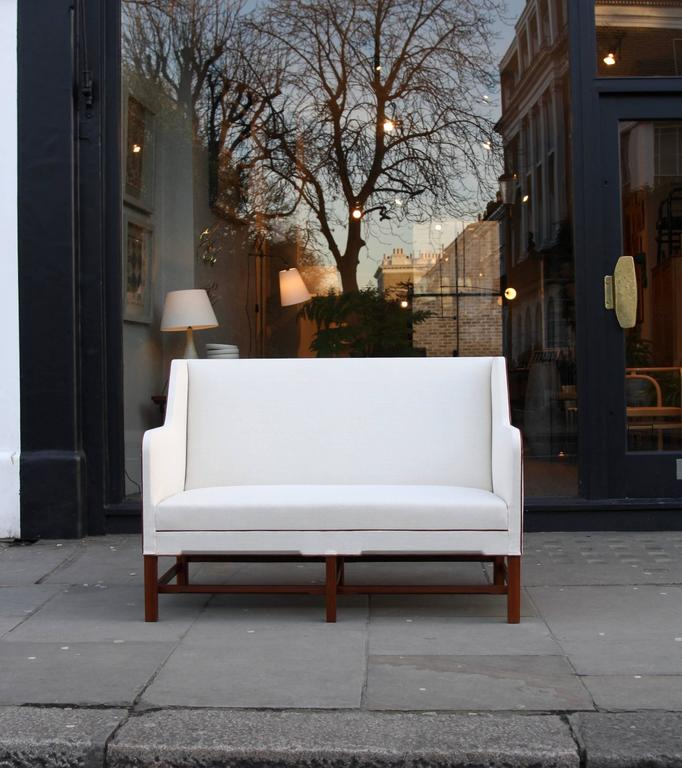 A two-seat 4118 settee designed by Kaare Klint and made by a master cabinetmakers Rud Rasmussen in Denmark, circa 1940. The exquisitely sharp yet flowing lines of the sofa make the high-level of consideration gone into its design and the quality of