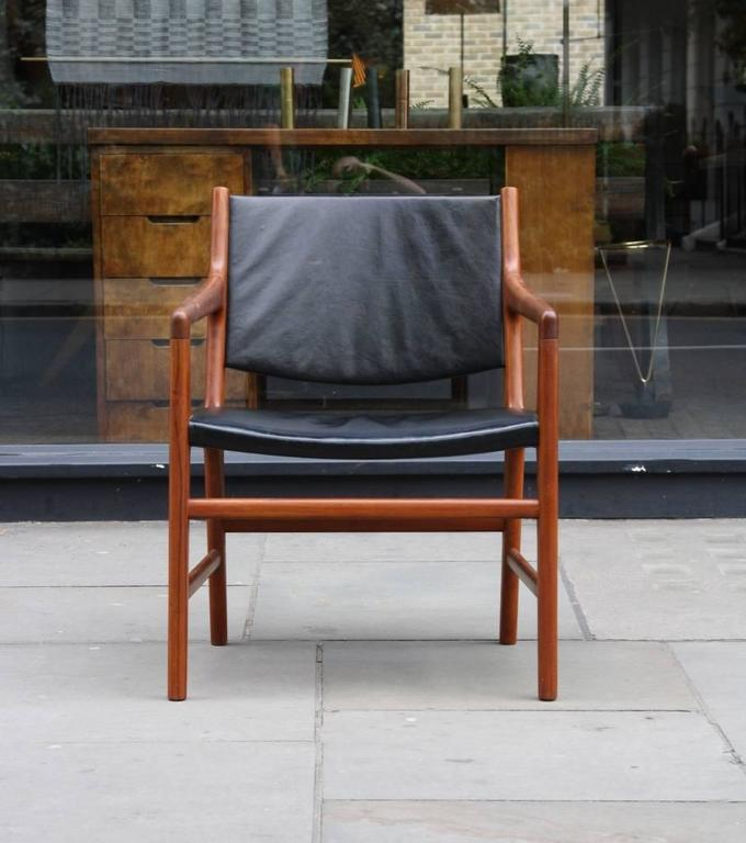 Armchair model JH507 designed in 1952 by Hans Wegner and made by Johannes Hansen. In solid hand carved teak, the chair has the original black leather on seat and back. This design was produced in few units and differs from the less rare JH525 for
