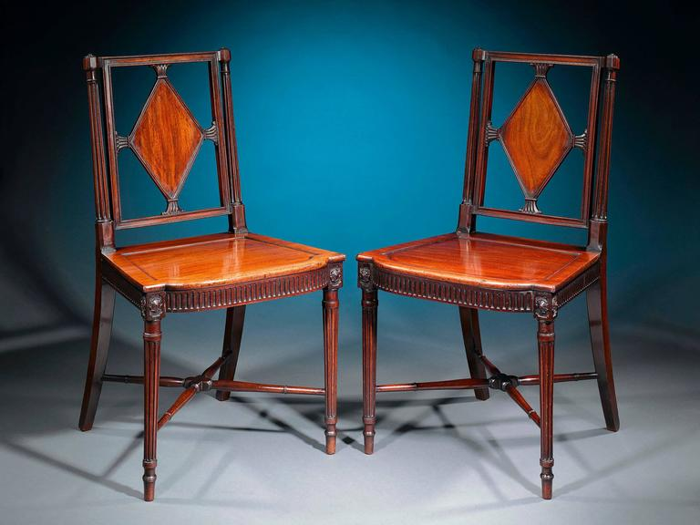 A fine pair of George III era mahogany hall chairs of exceptional craftsmanship and condition. Each masterfully carved seat is constructed with a rectangular back adorned with a lozenge panel between reeded columns. The solid seats are accentuated