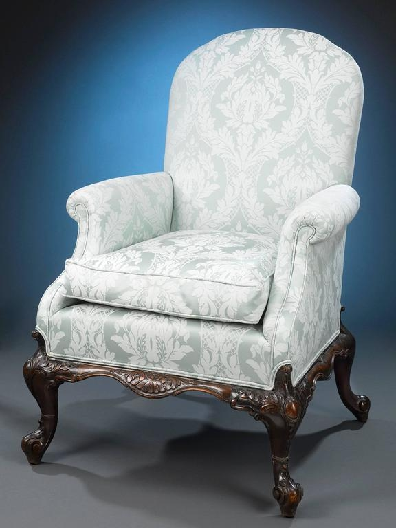 This Classic and highly desirable pair of George II-style armchairs is crafted of luxurious Cuban mahogany. Their large, yet elegant design is bolstered by beautifully upholstered arms, seats and backs, and fully carved cabriole legs reminiscent of