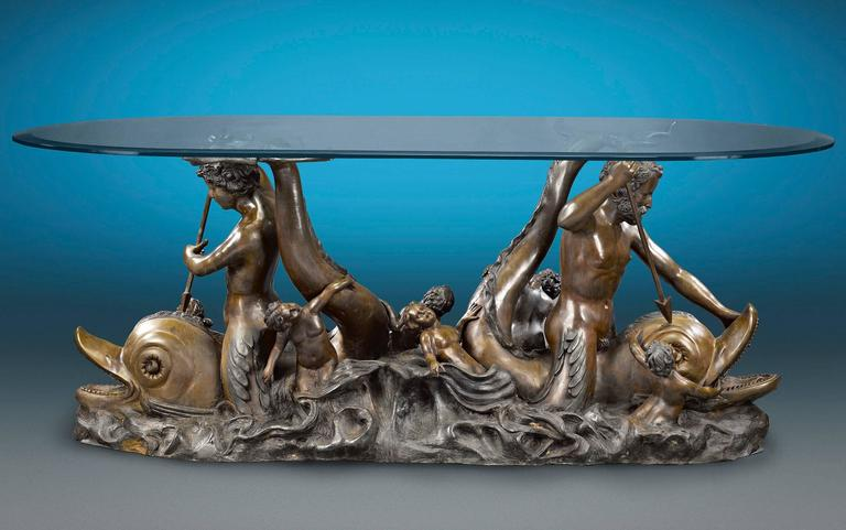 A merman and mermaid are astride a pair of dolphins in this incredible bronze sculptural table. As the merpeople spear their pray, they are joined by several putti enveloped by tumultuous waves. Its sleek glass top allows the opulent bronze to be