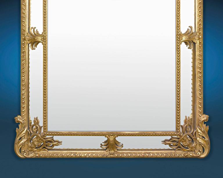 This stately Louis XV Revival French mirror features and elegant and intricately carved giltwood frame. The mirror is a study in Rococo glamour, with its asymmetrical, foliate decoration, C-scrolls, and cherub and bird accents. Highly unique and