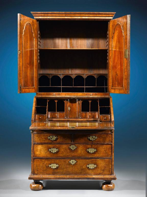 Queen Anne period furnishings such as this walnut secretary are incredibly rare and important examples of English cabinetmaking. This secretary is of the most outstanding caliber, boasting desirable double bonnet, mirrored cabinet doors and later