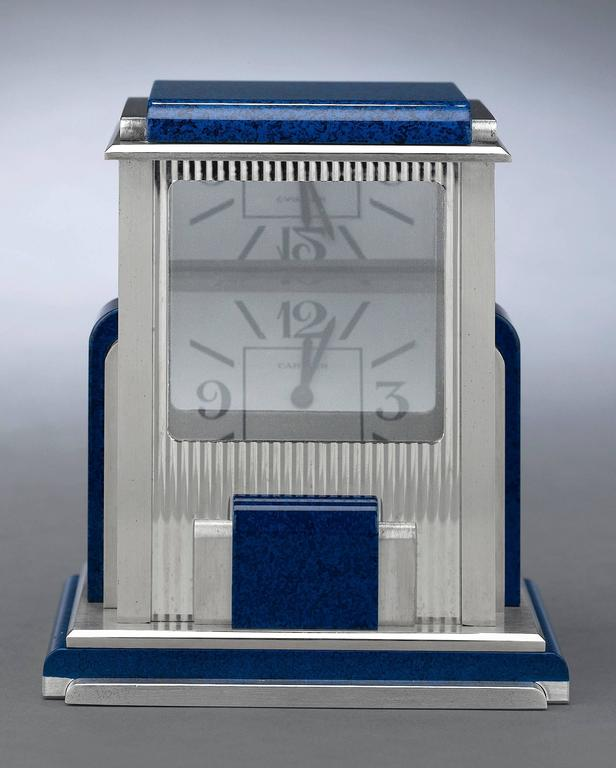 """A work of exceptional engineering and stylish artistry, this mystery clock by Cartier is known as a """"prism"""" clock. Crafted in a sleek Art Deco style with simulated lapis lazuli accents, this silver-plated desk clock is equipped with a set of quartz"""