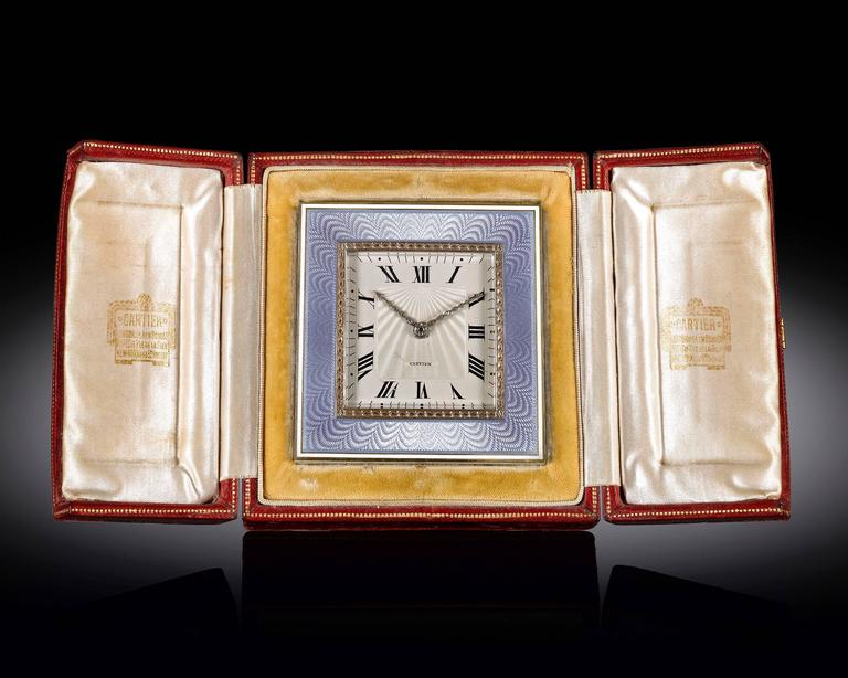 This elegant desk clock by Cartier features a soft blue guilloché enamel and gold frame. With Roman numerals marking the hours, the dial's radiant guilloché pattern is well-complemented by hands studded with fine white diamonds. An outstanding
