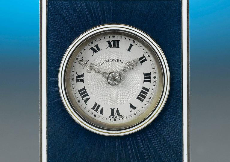 This luxurious and rare table clock is the essence of Art Deco style. Retailed at the renowned J. E. Caldwell & Co., this exceptional timepiece is comprised of a French clock movement. Guilloché enamelling in the most luxurious azure color covers