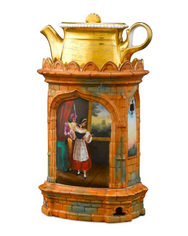 This excellent porcelain veilleuse is crafted in the form of an orange brick Gothic church, with hand-painted scenes, and is comprised of a demitasse teapot on a warming stand, inside which a small candle or oil is lit inside, keeping the tea in the