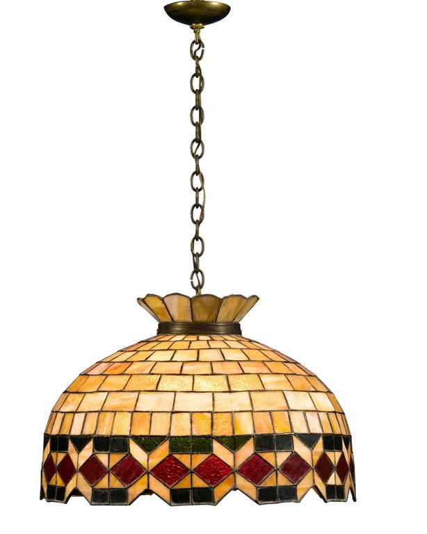 This impressive hanging light features carefully designed stained glass craftsmanship. Fitted with a four-way switch, this exceptional piece commands attention at first sight with its scalloped neck and colorful geometric motif. A star-shaped border