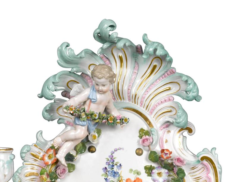 This enchanting pair of Meissen sconces exhibits the finest artistry for which this famed porcelain firm is known. Decorated with Meissen's hallmark hand-painted intricacy, with delicate applied flowers and garland-bearing cherubs, the sconces are