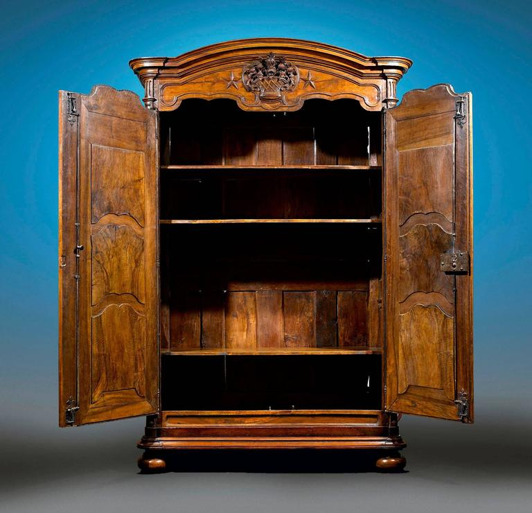 This monumental Louis XV armoire exhibits the rare beauty of French Provincial furniture. Crafted of lustrous walnut, this armoire features double doors, one of which opens with the original key, while the other opens with an interior latch.