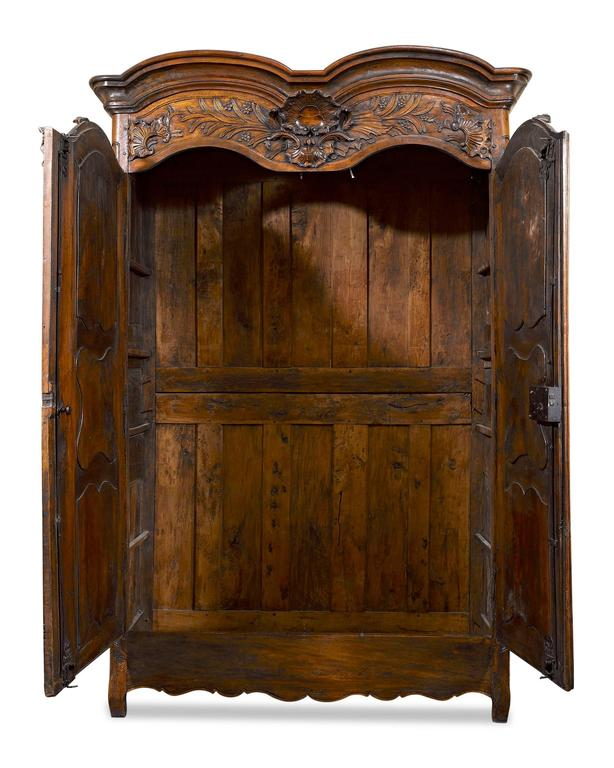 This majestic French walnut armoire is a stunning example of the Provincial style. Standing nearly nine feet high, this rare armoire featuring splendid rocaille carvings above its double doors and a wonderfully rich patina. Original mountings,