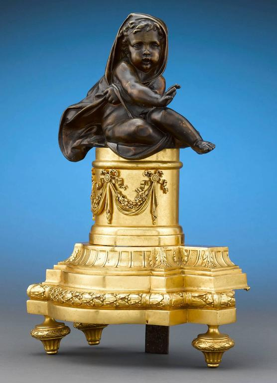 This wonderful pair of Louis XVI-style bronze chenets features patinated, cloaked cherub figures seated on ornate gilt bronze plateau and keeping themselves warm by the fire. Chenets, or andirons, were a staple in well-appointed homes, and were