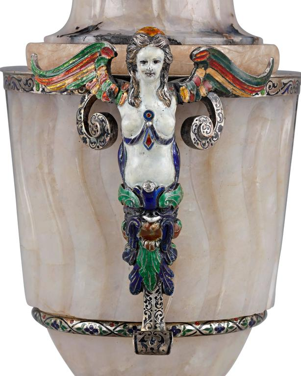 A glorious example of 19th century Viennese craftsmanship, this beautiful covered urn is hand-wrought from exquisite agate. Majestic silver mounts feature brilliant enameling of exceptional quality, with a pair of figural handles in the form of