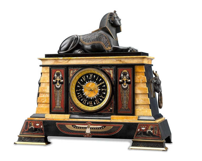 This Egyptian Revival clock garniture by J. E. Caldwell & Co. of Philadelphia is almost identical to the set that is housed in the collection of the Metropolitan Museum of Art. Composed of a clock and two obelisks, this garniture is crafted of