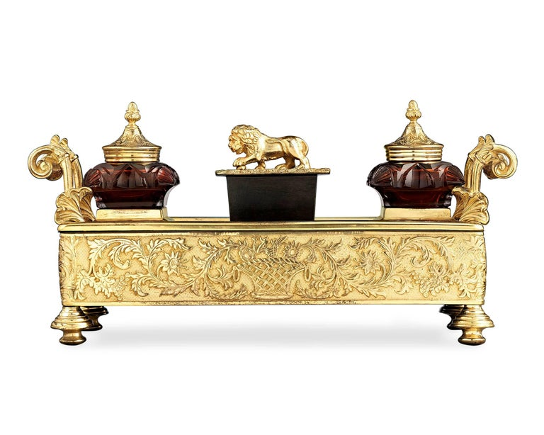 Fine bronze ormolu is beautifully contrasted by cranberry cut-glass in this Regency-period inkwell. This elegant desk accessory features a pair of removable glass inkwells, a wafer box surmounted by a gilt lion finial and a pen tray adorned with a