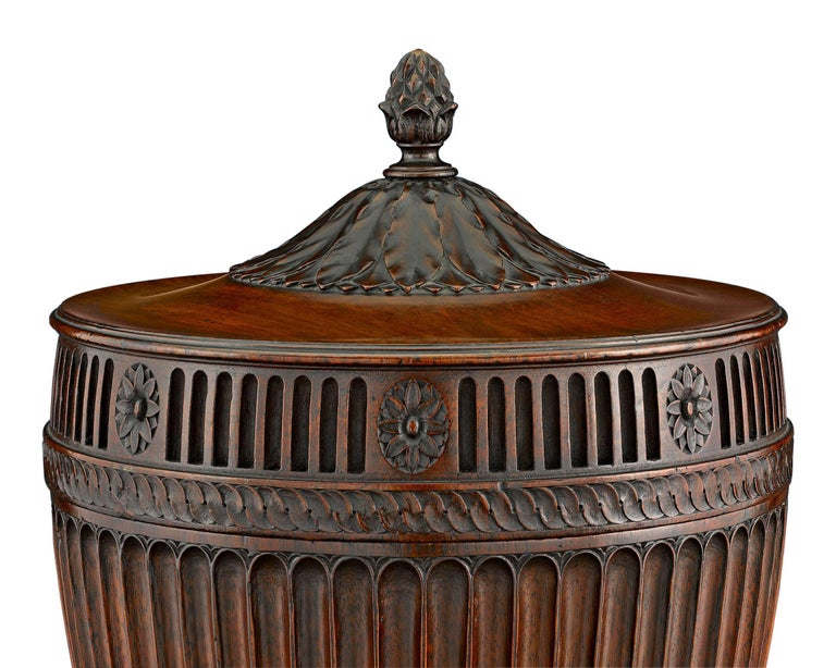 Exceptional carving and a rich, warm patina distinguish these rare George III-period mahogany urns. These Neoclassical vessels, highlighted by fluted, gadrooned, anthemion and acanthus motifs, feature their original spigots and linings. Most likely