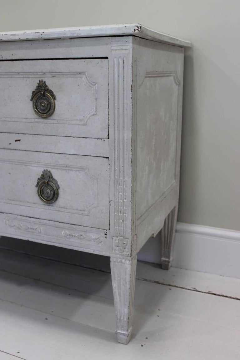 A late 18th century Louis XVI two-drawer commode in the neoclassical style, (walnut with later white paint).