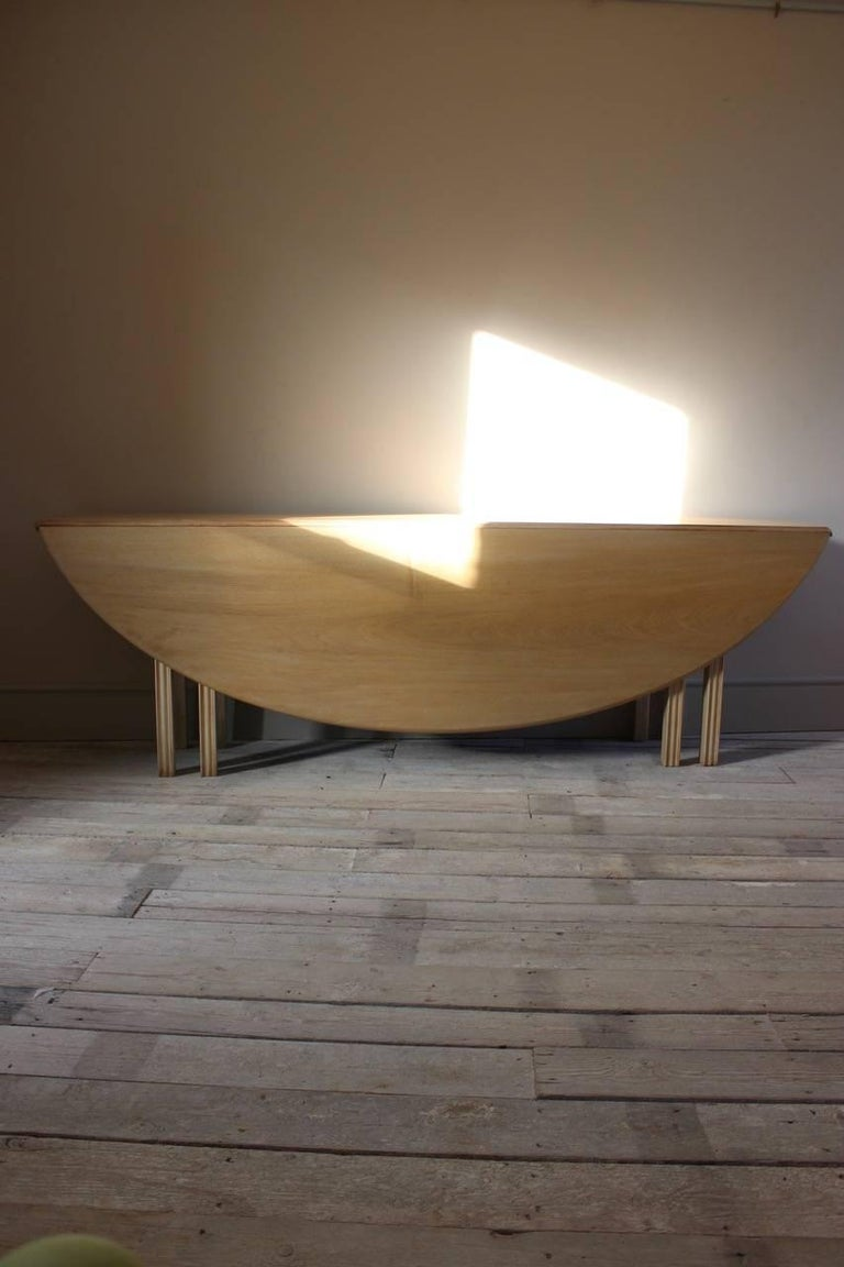 A large circa 1950s bleached mahogany folding oval dining table of Irish 'hunt' or 'wake' style.  Measures: Depth: 42cm deep (closed) x 162cm deep (open).