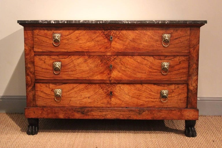 A good quality and well-proportioned Empire commode of highly-figured walnut with a marble top and lion-mask handles, French, early 19th century.