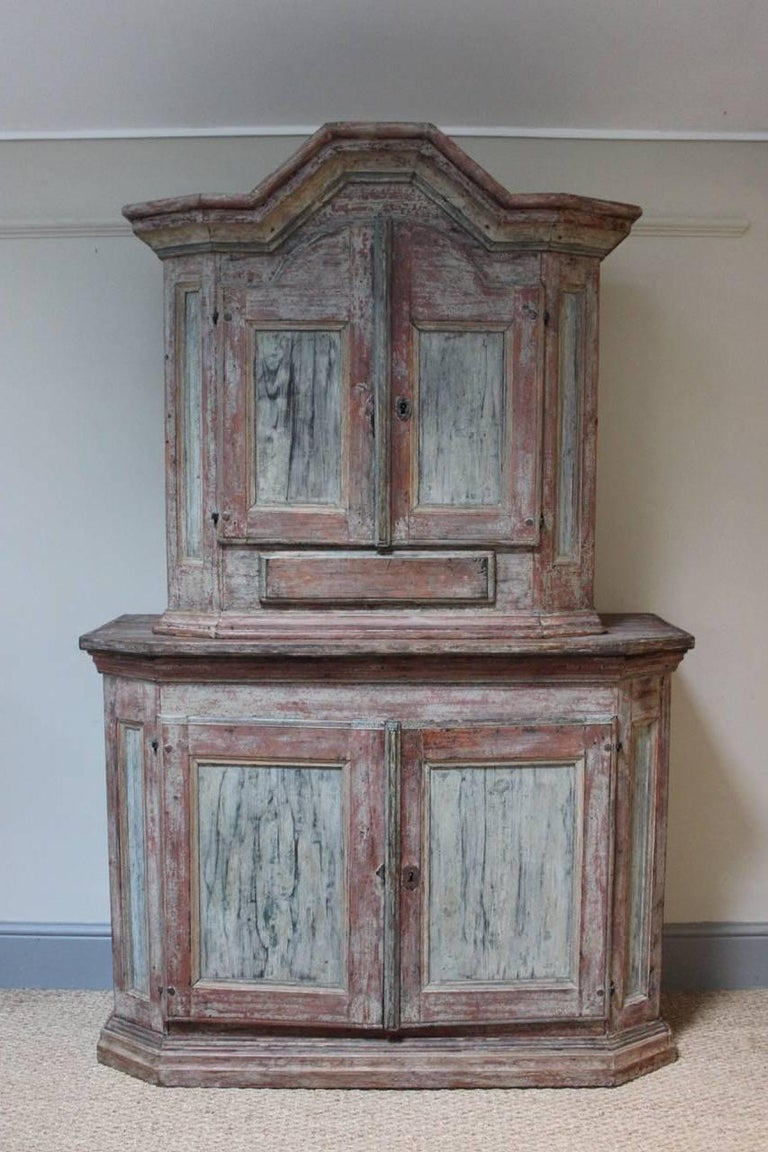 A very charming 18th century painted Swedish baroque cupboard, dry scraped to reveal the original paint, of elegant design, offering plenty of storage , with a single drawer.