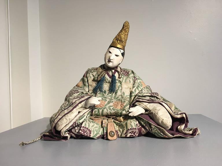 Two exquisite Japanese musha ningyo dolls, crafted as courtiers.  The older man can be identified as the historical figure Takenouchi no Sukune, a trusted court advisor to the warrior Empress Jingu and later, her son Ojin. He is always portrayed as