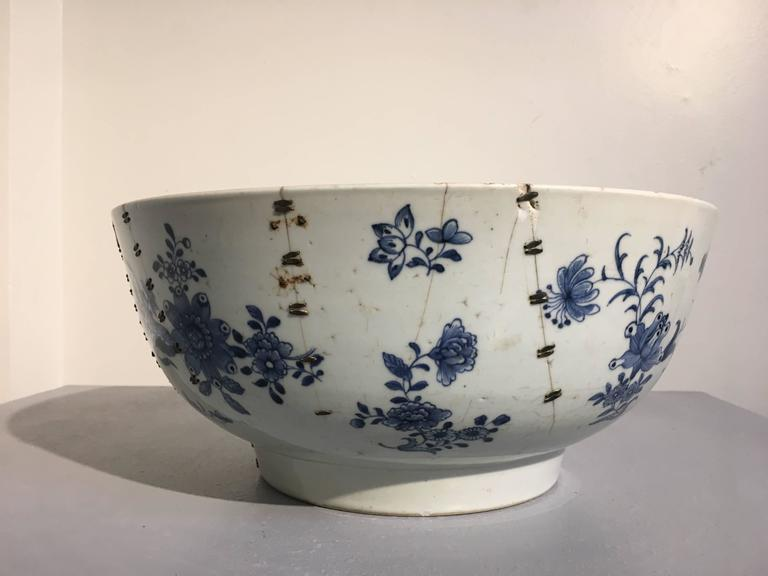 A remarkable large Chinese export blue and white punchbowl painted with a floral and brocade design, and featuring a stunning staple repair.  While of large size and beautifully painted, what makes this piece exceptional is the staple repairs on