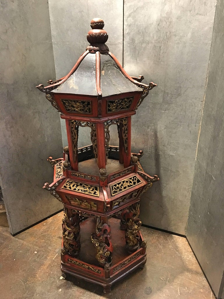 A large two-tiered hexagonal Chinese architectural model of a pagoda or pavilion, Qing Dynasty, late 19th century.  The bottom tier with columns surrounded by writhing dragons that have been carved separately, and can rotate on the column. Scenes of
