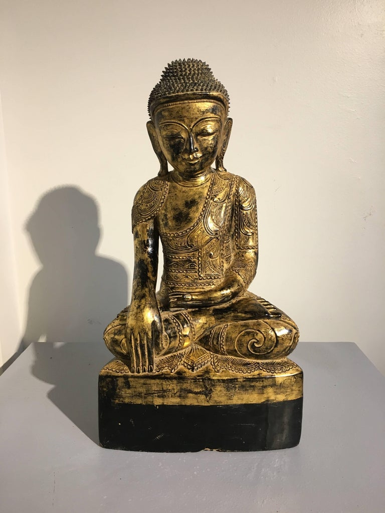 A sublime and rare late 18th century Burmese Ava period carved, lacquered and gilt Buddha. The historical Buddha, Shakyamuni, is portrayed in bhumisparsha mudra, the gesture of calling the Earth to witness, commemorating the moment the Buddha