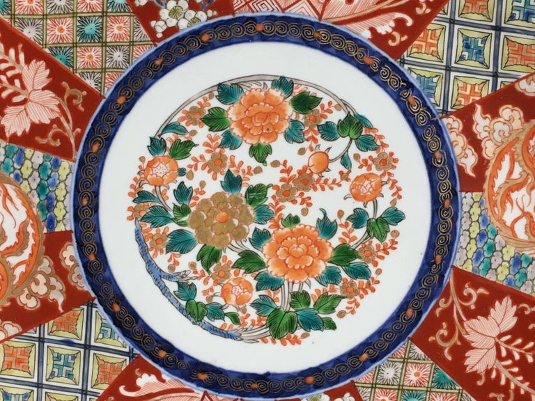 A striking Japanese Imari charger, painted in vibrant enamels of red, blue, green and orange. The patterning reminiscent of a chrysanthemum blossom. Each